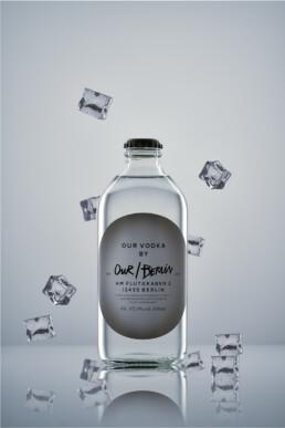 eine Flasche von Our Vodka Berlin mit fliegenden Eiswürfeln